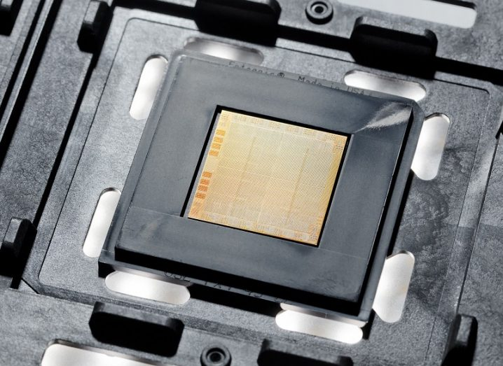 The IBM Power10 chip. It looks like a small, square, brown chip placed inside a black piece of plastic.