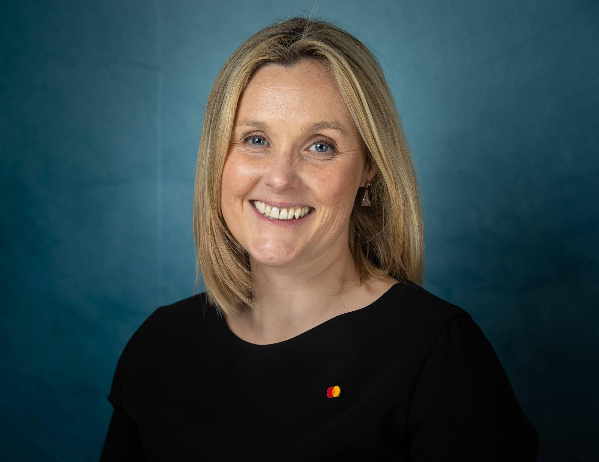 Sarah Cunningham of Mastercard is smiling into the camera against a dark blue background.