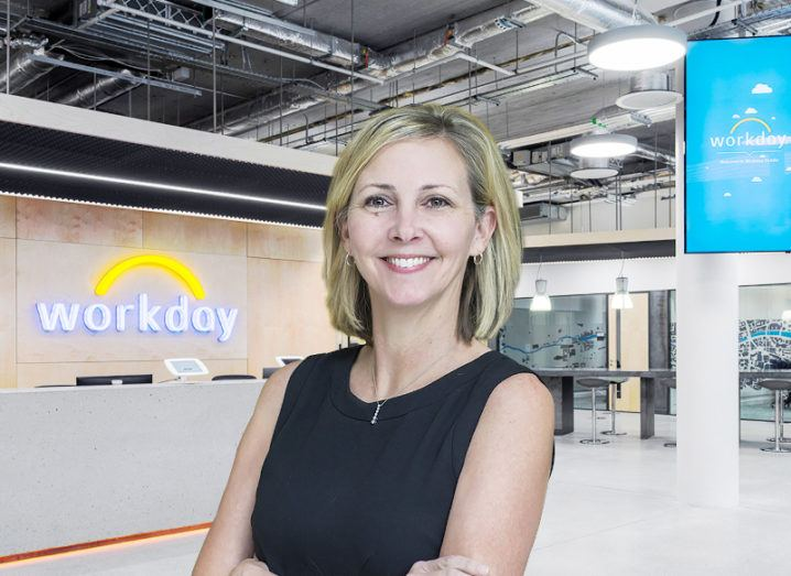 A woman with short blonde hair smiles at the camera, in front of an office background with the Workday logo on the wall.