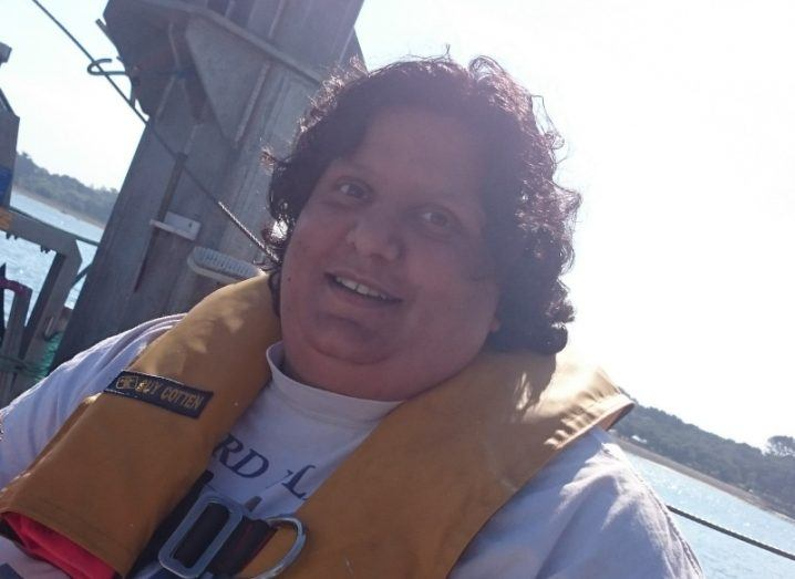 A woman on a boat in the ocean wearing a white T-shirt and an inflatable yellow life jacket smiles at the camera.