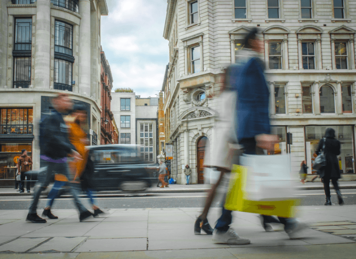 Busy pedestrians walking down a street carrying bags from retail stores.