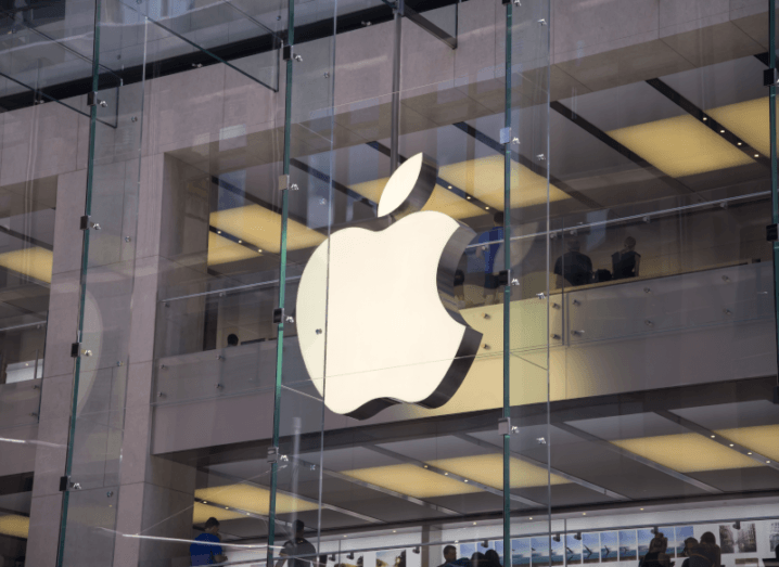 The Apple logo lit up in front of a glass window.