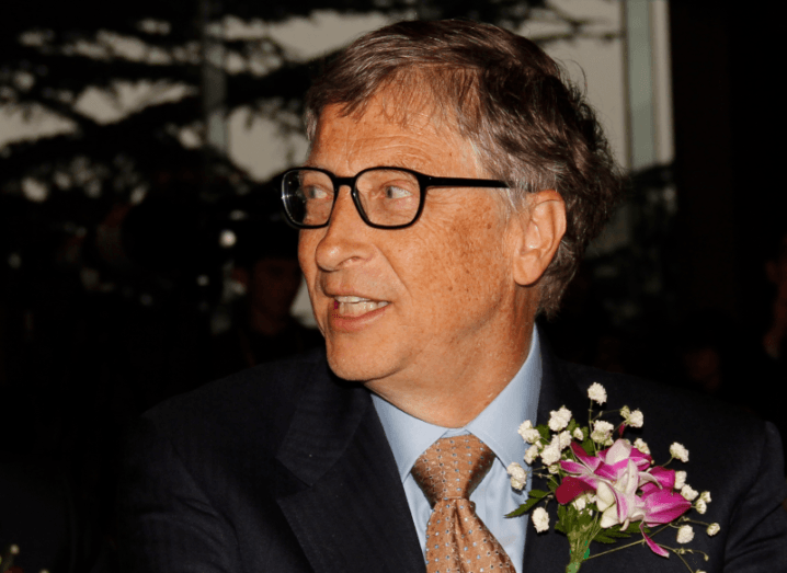 Bill Gates wearing black glasses and a suit with flowers attached to his lapel.