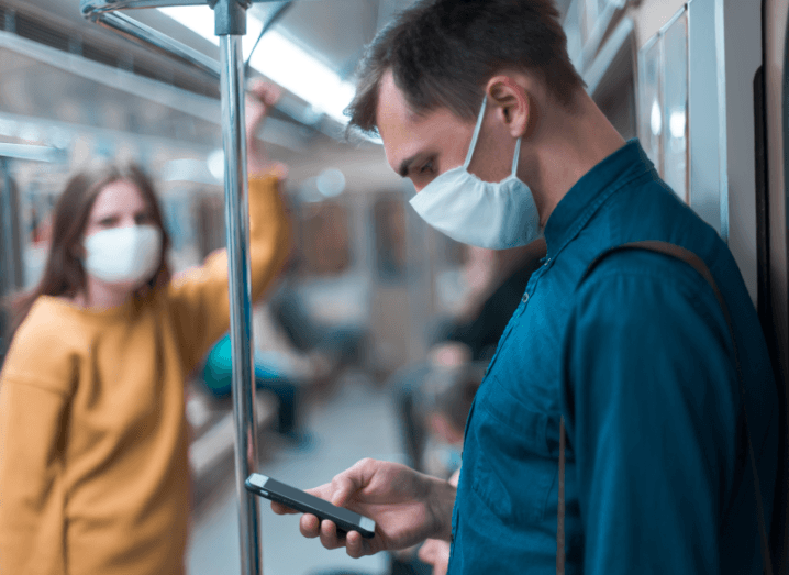 A man in a blue shirt standing on a train wearing a white mask while using his phone. There is a woman in the background who is also wearing a white mask, with a yellow sweater.