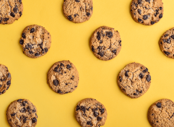 Cookies spaced out in rows in front of a yellow background.