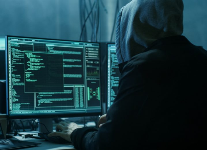 A hooded hacker sits at desk in a dark room. He is working at a monitor with a lot of green code on it.