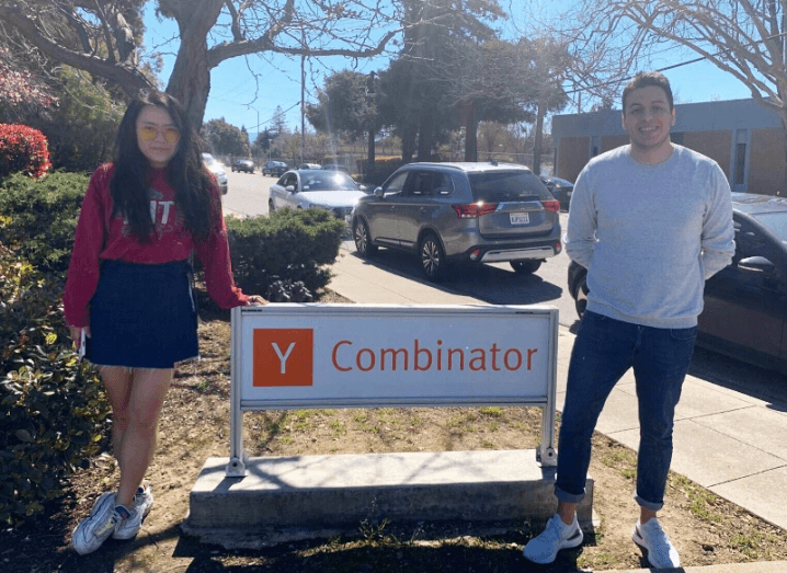 A young woman and a man stand beside a Y Combinator sign on a street. The woman is wearing a red shirt and blue skirt and the man is wearing a white shirt and blue jeans.