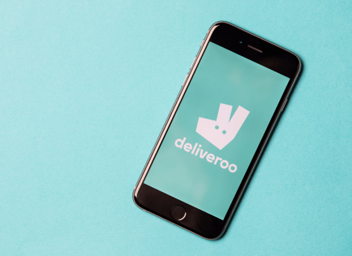 The Deliveroo logo displayed on an iPhone screen in front of a turquoise background.