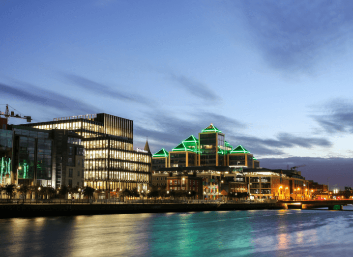 A view of the quays along the Liffey in Dublin at dusk. Tall buildings are lit up brightly.
