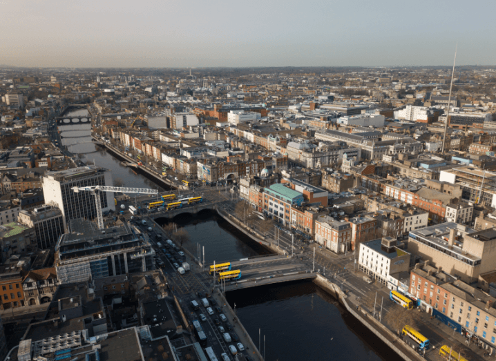 An aerial view of the Liffey river in Dublin city centre, with cranes above buildings and buses driving along the quays.