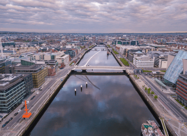 An aerial view of the Liffey river in Dublin. The Convention Centre is on the right, while office buildings are lined up along the left. In the middle of the image is the Samuel Beckett bridge.