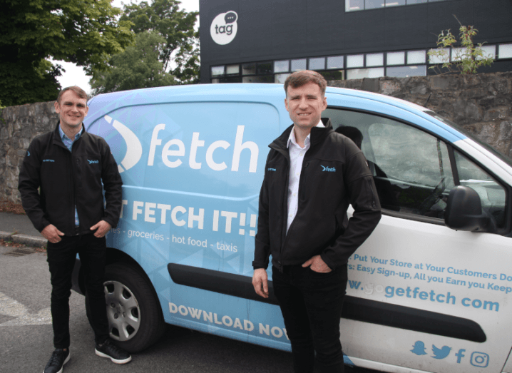 Two men standing beside a light blue van with Fetch signage printed on the side of it. Both of the young men are wearing Fetch jackets.
