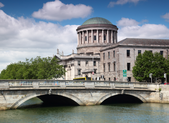 The four courts building in Dublin City centre, with a large stone bridge in the foreground of the image.