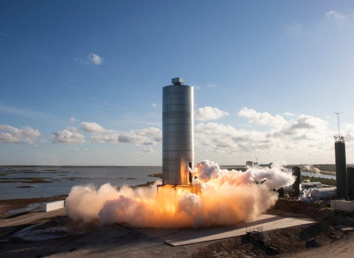 A large cylindrical SpaceX spaceship launches from the ground against a blue sky. Plumes of smoke surround the base.