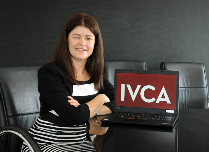 A woman wearing a black and white dress sits in a conference room beside a laptop with the letters IVCA displayed on its screen.