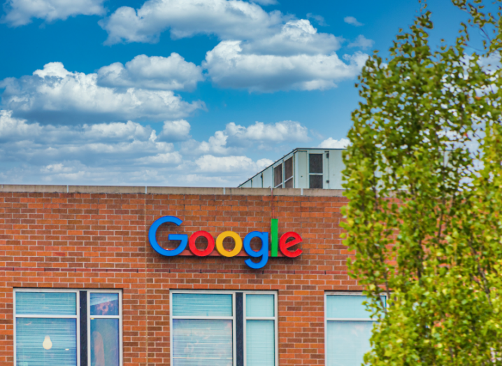 The Google logo on the side of a red brick building. There is a tree in front of the building.