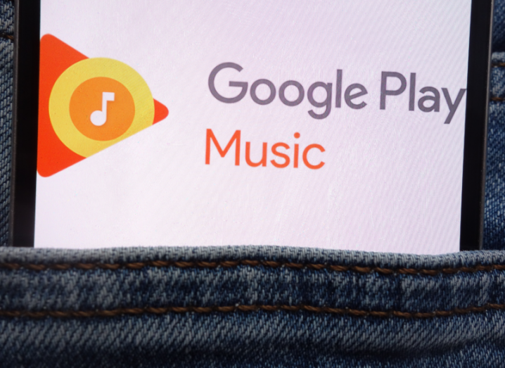 A smartphone in the pocket of denim jeans, displaying the Google Play Music logo on its screen.