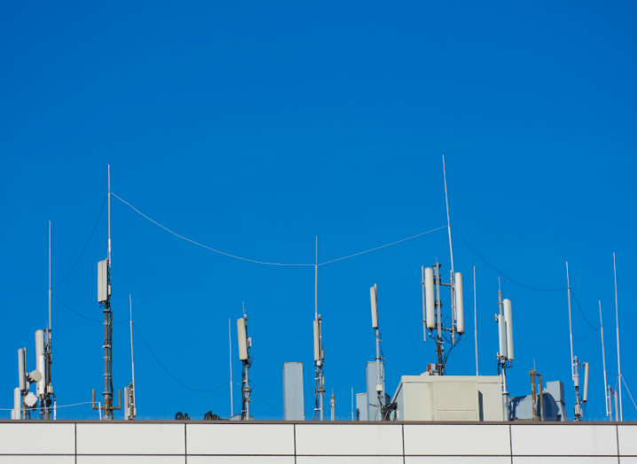 A blue sky above phone masts.