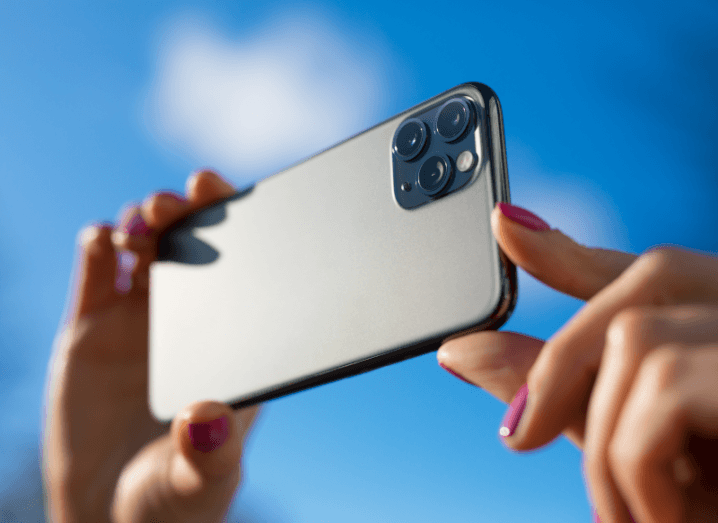 A person holding an iPhone in the air taking a photo in front of a blue sky.