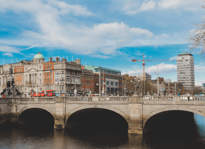 O'Connell bridge in Dublin city centre, with Liberty Hall and O'Connell street visible in the background, under a blue sky.