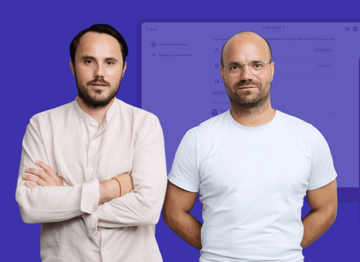Two men in white shirts standing in front of a purple background.