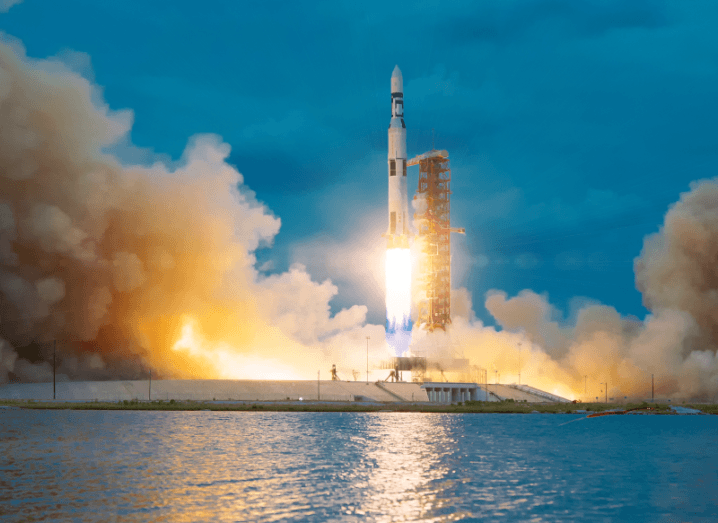 A rocket launching in front of a body of water, surrounded by smoke.