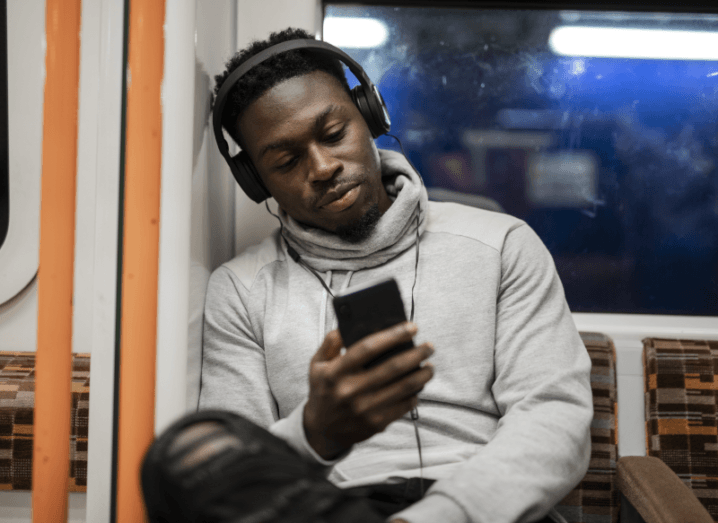 A man wearing a grey hoodie and black headphones sits on a train looking at his phone.