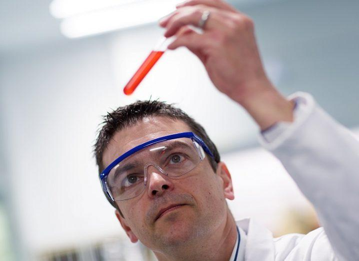 Marc Devocelle wearing safety glasses while holding up a test tube containing a red liquid.