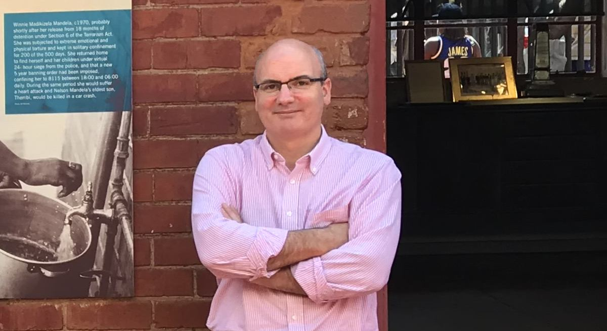 Mike Feerick is wearing a pink shirt while standing in front of a red brick wall and smiling into the camera.