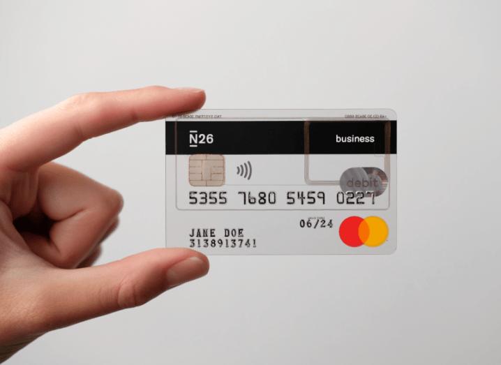 A person holding a transparent debit card.