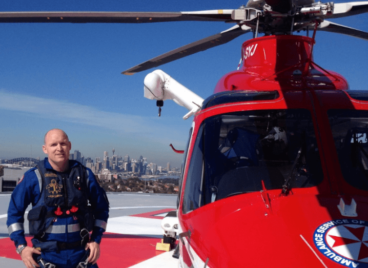 A man with a shaved head wearing a navy paramedic suit is standing beside a red helicopter on a helipad above a cityscape.