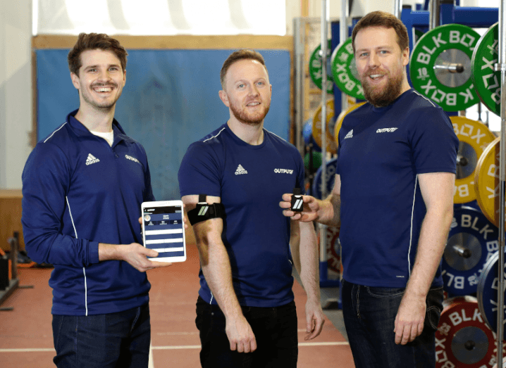 Three men in navy tops stand holding an iPad and a wearable device.
