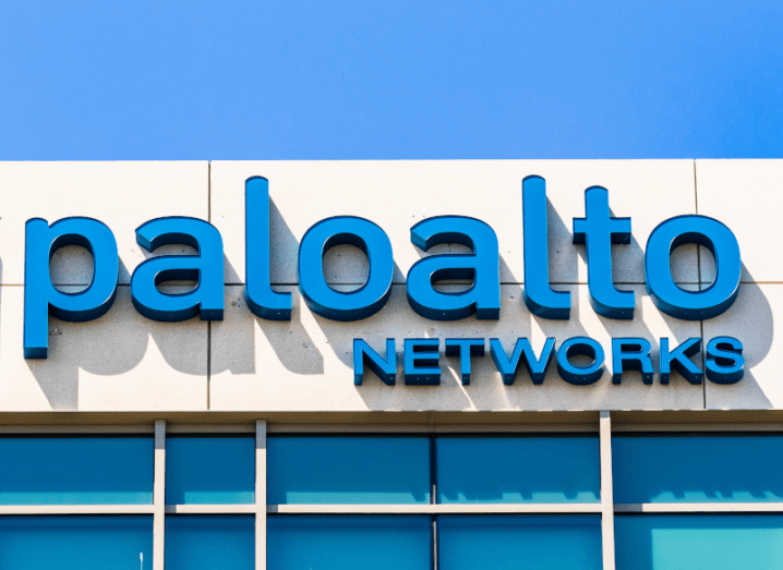 The Palo Alto Networks logo on the front of an office building, under a blue sky.