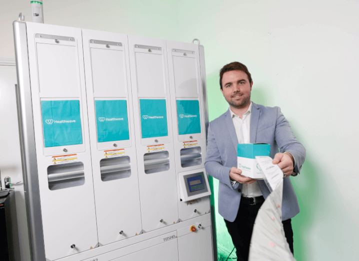A man in a grey blazer standing beside a white machine that dispenses packets of pills.