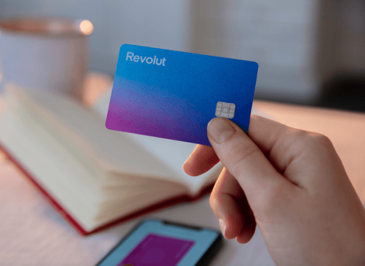 A person holding a Revolut card in front of a table with an open book on it.