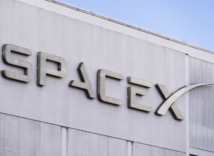 The SpaceX logo on the front of a concrete building.