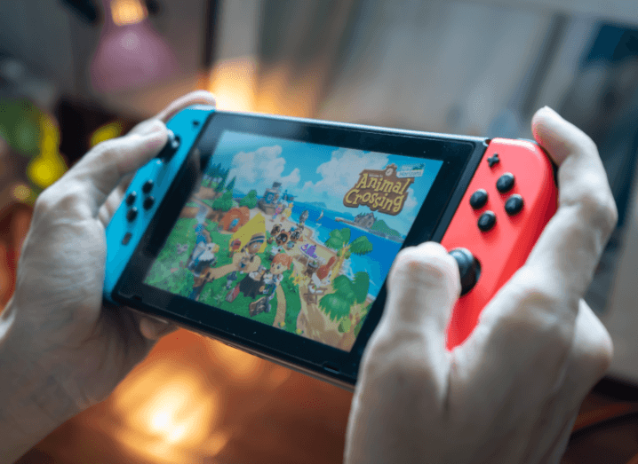 A person holding a Nintendo Switch with Animal Crossing on screen.