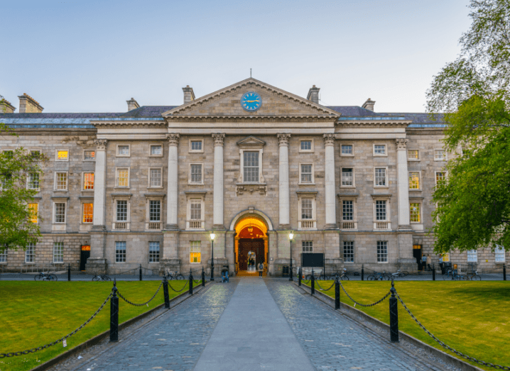 Parliament square inside the gates of Trinity College Dublin. A large white building with neat lawns and trees in front of it.