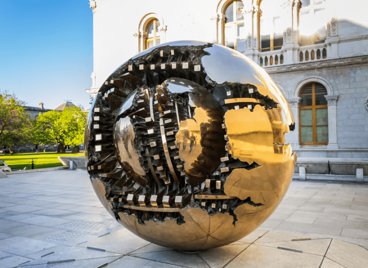 A large bronze sculpture of a sphere in front of an old building.
