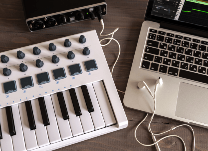 A midi keyboard, an audio interface and a Mac laptop on a wooden surface.