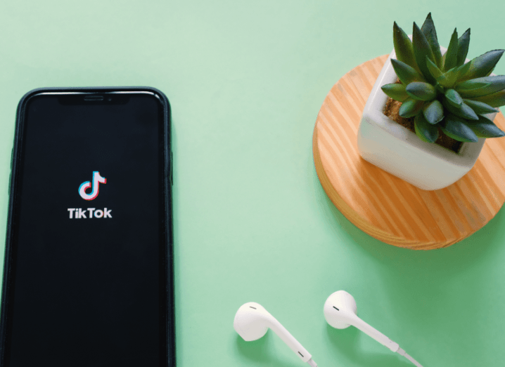 The TikTok logo displayed on a smartphone screen on a green surface, beside a pair of earphones and a small potted plant.