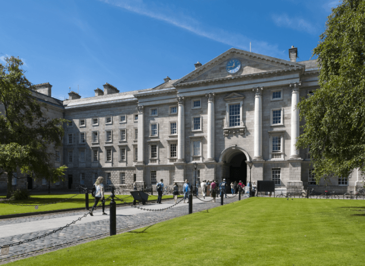 The building at the front gate of Trinity College Dublin, with a lawn and leafy trees on either side of its entrance.