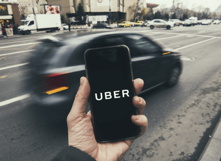 A person holding a smartphone in front of them with the Uber logo displayed on the screen as a car goes by quickly on the street ahead of the phone.