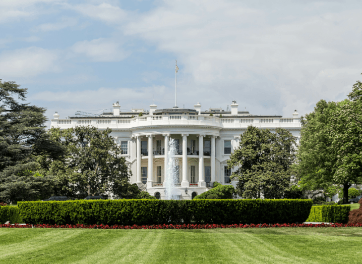 An image of the White House, a large white residential property in front of a neat lawn, with trees and hedges in front of it.