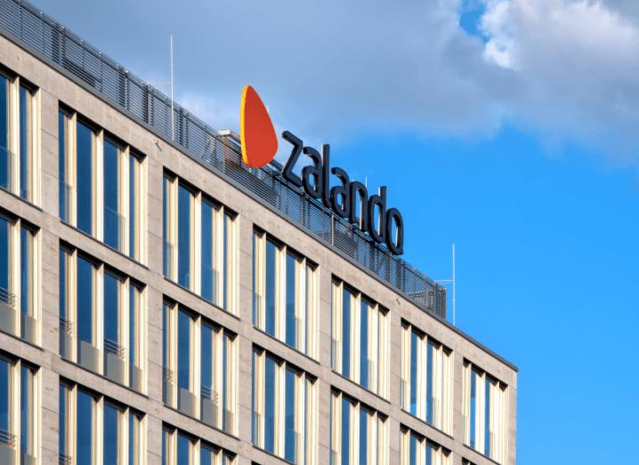 The Zalando logo on the top of an office building underneath a blue sky.