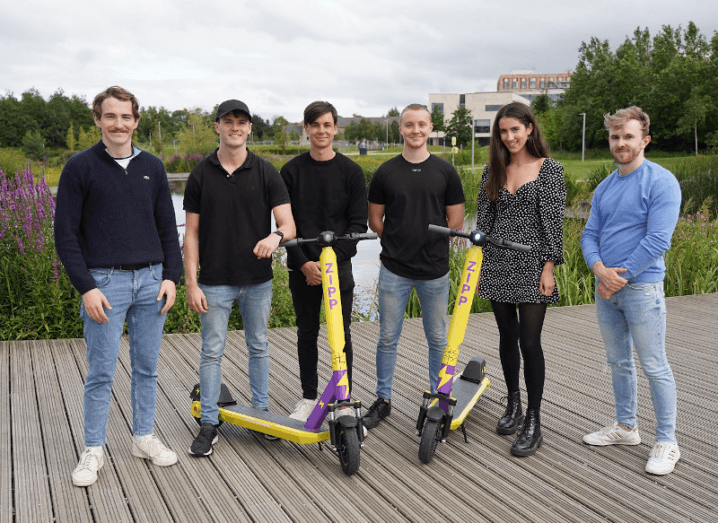A group of young people standing on a wooden deck in front of UCD's lake. In front of the six people are two yellow e-scooters with the purple Zipp logo on them.