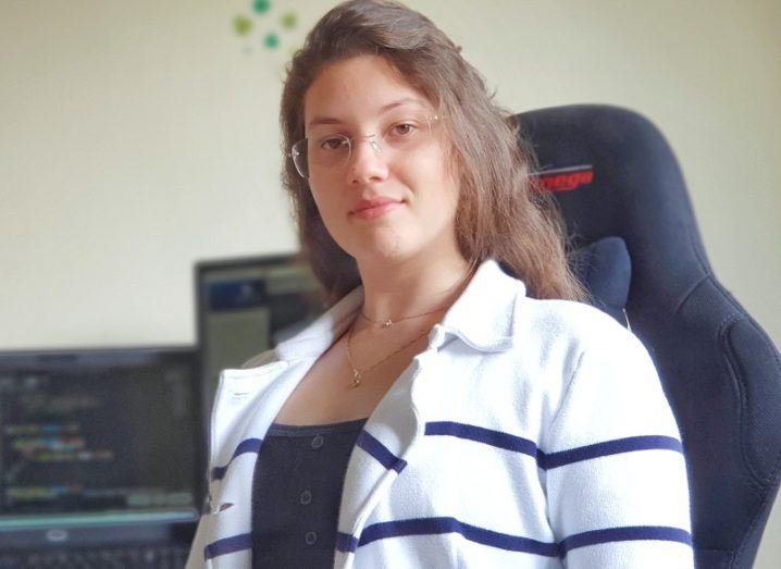 Adrielle Nazar Moraes in a white top and sitting on an office chair.