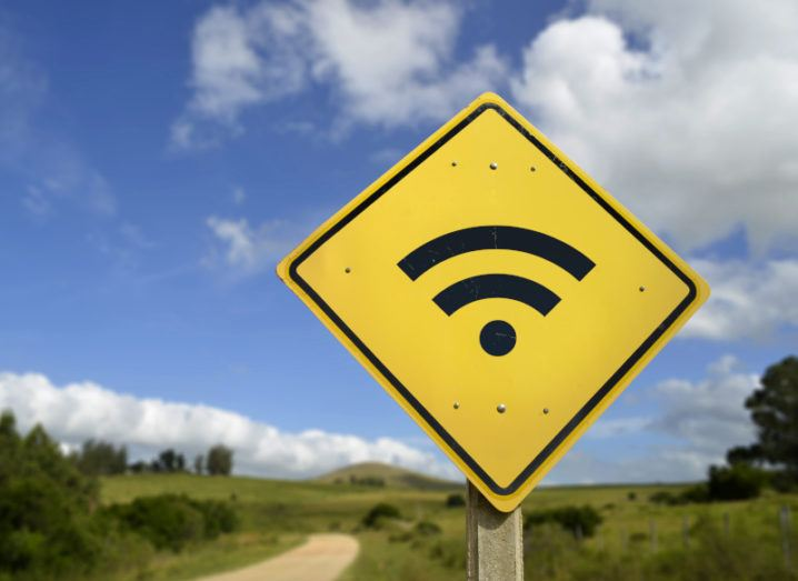 A bright yellow road sign on a rural road is displaying the symbol for Wi-Fi access.