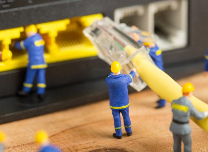 Miniature models of technicians working to plug an ethernet cable into a router.