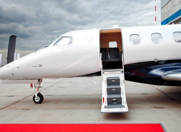 Door and footladder open on a parked private jet at an airport.